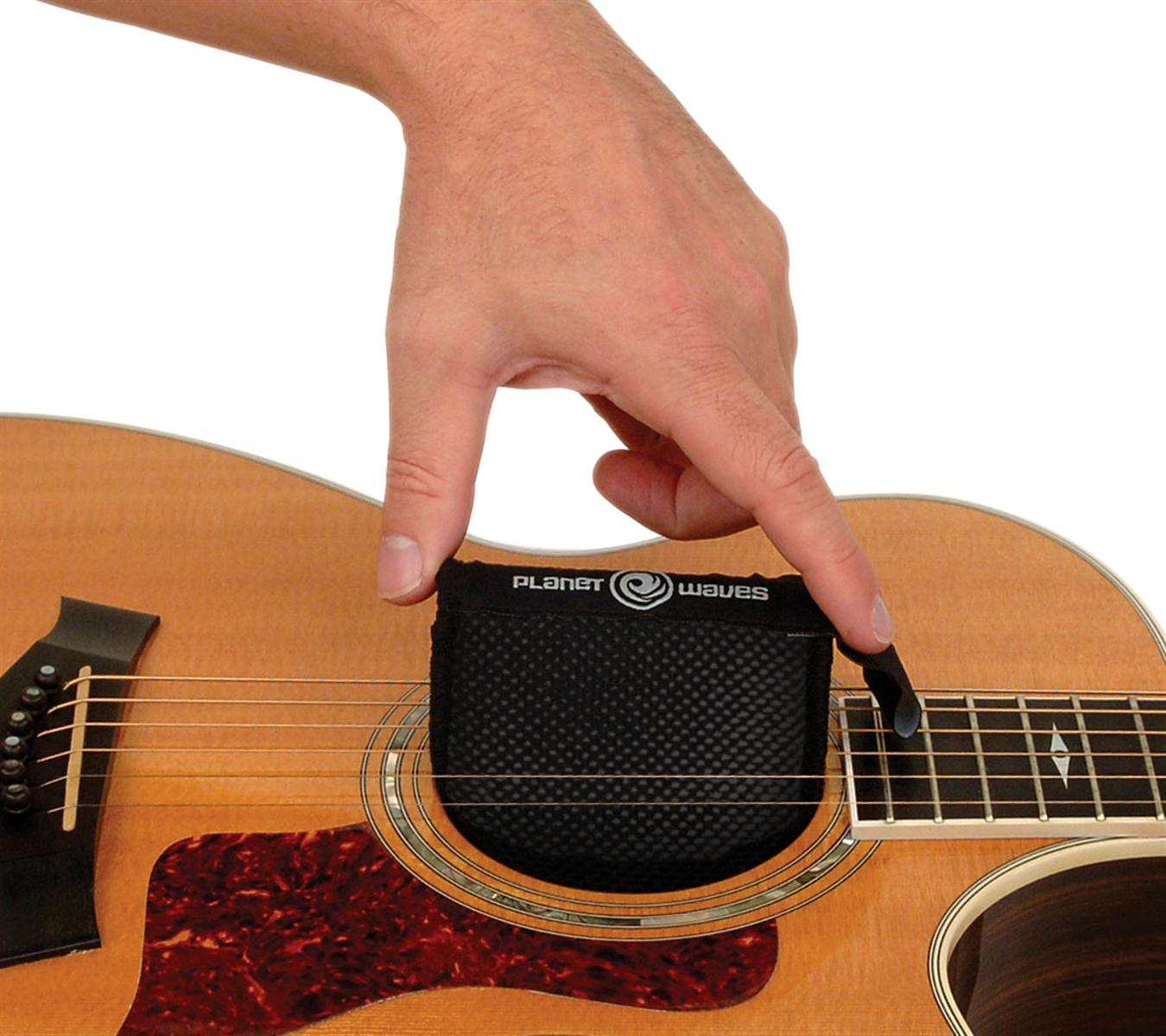 A person holding a Planet Waves Humidipak inside the soundhole of an acoustic guitar to maintain its humidity.